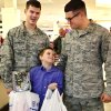 Bradley Disterlic, 10, a fifth grader at Ridgecrest Elementary School, holds two bags filled with clothing items after purchasing all the items, and looks up at two Air Force service members who were his shopping buddies. At left is Zach Rasmussen, 24. At right is Ken Lamendola, 25. More than 50 Department of Defense employees at Tinker Air Force Base teamed with students from various Mid-Del elementary schools Thursday morning, Dec. 5, 2013, on a storewide shopping spree at JC Penney store in Town Center Plaza on SE 29 Street in Midwest City. Photo by Jim Beckel, The Oklahoman