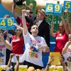 Joey Chestnut, center, wins the Nathan\'s Famous Fourth of July International Hot Dog Eating contest with a total of 69 hot dogs and buns, alongside Tim Janus, left, and Matt Stonie, right, Thursday, July 4, 2013 at Coney Island, in the Brooklyn borough of New York. (AP Photo/John Minchillo)