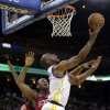 Golden State Warriors\' Carl Landry (7) shoots next to Philadelphia 76ers\' Lavoy Allen, middle, during the first half of an NBA basketball game in Oakland, Calif., Friday, Dec. 28, 2012. (AP Photo/Marcio Jose Sanchez)