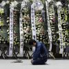 Photo - A mourner pays tribute to the victims of the sunken ferry Sewol near condolence flowers during a temporary memorial at the auditorium of the Olympic Memorial Museum in Ansan, south of Seoul, South Korea, Thursday, April 24, 2014. Divers made their way deeper Thursday into the submerged wreck of a ferry that sank more than a week ago as the death toll neared 160 and relatives of the more than 140 still missing pressed the government to finish the grim task of recovery soon. (AP Photo/Lee Jin-man)