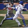 Photo - Atlanta Braves starting pitcher David Hale, left, tags out New York Mets' Curtis Granderson during the second inning of a baseball game, Sunday, April 20, 2014 in New York. (AP Photo/Seth Wenig)