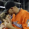 Photo - Miami Marlins starting pitcher Jose Fernandez, right, kisses his grandmother Olga Fernandez, of Cuba, left, following the Marlins' 10-1 victory over the Colorado Rockies during an opening day baseball game, Monday, March 31, 2014, in Miami. (AP Photo/Lynne Sladky)