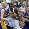 Photo - Los Angeles Lakers' Chris Kaman, left, and Steve Nash, right, defend as Dallas Mavericks' Samuel Dalembert of Haiti looks for a shot opportunity in the first half of an NBA basketball game, Tuesday, Nov. 5, 2013, in Dallas. (AP Photo/Tony Gutierrez)
