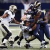 Photo - St. Louis Rams defensive end Robert Quinn (94) is pulled down by New Orleans Saints running back Pierre Thomas, center, after recovering a fumble as Saints' Charles Brown, left, watches during the third quarter of an NFL football game Sunday, Dec. 15, 2013, in St. Louis. (AP Photo/Charles Rex Arbogast)