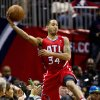 Atlanta Hawks point guard Devin Harris (34) jumps into the crowd to save the ball from going out of bounds in the first half of an NBA basketball game against the Miami Heat in Atlanta, Friday, Nov. 9, 2012. (AP Photo/John Bazemore)