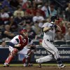 Photo - Minnesota Twins designated hitter Ryan Doumit (9) follows through with an RBI base hit as Atlanta Braves catcher Brian McCann (16) watches in the eighth inning of a baseball game Tuesday, May 21, 2013 in Atlanta. (AP Photo/John Bazemore)