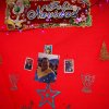 "Photo - A snapshot of Venezuela's President Hugo Chavez is surrounded by a trio of religious prayer cards and a sign that reads in Spanish; ""Merry Christmas"" on a red background hanging at a state-run market in Caracas, Venezuela, Friday, Dec. 28, 2012. The obsessive, circular conversations about Chavez's health dominate family dinners, plaza chit-chats and social media sites in this country on edge since its larger-than-life leader went to Cuba for emergency cancer surgery more than two weeks ago. The man whose booming voice once dominated the airwaves for hours at a time has not been seen or heard from since. (AP Photo/Fernando Llano)"