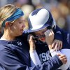 Edmond North assistant coach Kayla Jennings hugs dejected senior Madison Nordyke after she was out at first base for the final out of the game, ending her team\'s chance to advance in the Class 6A high school fast-pitch softball championship tournament at the Ball Fields at Firelake in Shawnee on Thursday, Oct. 17, 2013. Edmond North lost to Broken Arrow in the first round of the tournament. Photo by Jim Beckel, The Oklahoman.