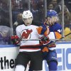 Photo - New Jersey Devils left wing Tuomo Ruutu (15) and New York Islanders defenseman Calvin de Haan (44) collide in the first period of an NHL hockey game on Saturday, March 29, 2014, in Uniondale, N.Y. (AP Photo/John Minchillo)