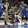 Charlotte Bobcats\' Kemba Walker, center, looks to pass as he is trapped by Minnesota Timberwolves\' Greg Stiemsma, left, and Derrick Williams, right. during the first half of an NBA basketball game in Charlotte, N.C., Saturday, Jan. 26, 2013. (AP Photo/Chuck Burton)