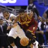 Photo - Cleveland Cavaliers' Kyrie Irving (2) goes after a loose ball in front of Orlando Magic's Jameer Nelson, left, during the first half of an NBA basketball game in Orlando, Fla., Wednesday, April 2, 2014. (AP Photo/John Raoux)