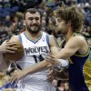 Photo - Minnesota Timberwolves' Nikola Pekovic of Montenegro, left, protects the ball from New Orleans Hornets defender Robin Lopez in the first quarter of an NBA basketball game Saturday, Feb. 2, 2013 in Minneapolis. (AP Photo/Jim Mone)