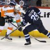 Philadelphia Flyers\' Harry Zolnierczyk (12) and Winnipeg Jets\' Tobias Enstrom (39) battle for control of the puck during the second period of an NHL hockey game in Winnipeg, Manitoba, Tuesday, Feb. 12, 2013. (AP Photo/The Canadian Press, Trevor Hagan)