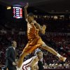 Texas Demarcus Holland leaps on a pump fake by Oklahoma Sooner Jordan Woodard (10) as the University of Oklahoma Sooners (OU) men play the Texas Longhorns (TU) in NCAA, college basketball at The Lloyd Noble Center on Saturday, March 1, 2014 in Norman, Okla. Photo by Steve Sisney, The Oklahoman
