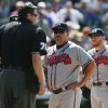 Photo - Atlanta Braves manager Fredi Gonzalez, second from right, looks on as home plate umpire Jordan Baker, front left, tries to restore order after Colorado Rockies' batter Corey Dickerson was hit by a pitch which triggered the ejection of Rockies manager Walt Weiss in the eighth inning of the Rockies' 10-3 victory in a baseball game in Denver, Thursday, June 12, 2014. (AP Photo/David Zalubowski)