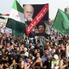 In this picture taken on Sunday October 21, 2012, anti-Lebanese government protesters, wave the Syrian revolutionary flags and hold portraits of Lebanese Prime Minister Najib Mikati, up, and for Hezbollah\'s leader Sheik Hassan Nasrallah, down, with Arabic words read: