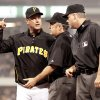 Second-base umpire Tim Tschida, center, gets between Pittsburgh Pirates manager John Russell, left, and first-base umpire Tim Timmons, right, after Timmons threw Russell out of the game after Russell argued a call on Saturday. AP photo