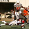 Oklahoma State\'s Tracy Moore leaps over Louisiana-Lafayette\'s Dwight Bentley (5) during Saturday\'s game in Stillwater. Photo by Sarah Phipps, The Oklahoman