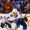 Chicago Blackhawks\' Niklas Hjalmarsson, left, of Sweden, and Vancouver Canucks\' Mason Raymond battle to get to the puck during the first period of an NHL hockey game in Vancouver, British Columbia, on Friday, Feb. 1, 2013. (AP Photo/The Canadian Press, Darryl Dyck)