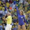Photo - Rapper Pitbull, left, and Brazilian singer Claudia Leitte perform during the opening ceremony ahead of the group A World Cup soccer match between Brazil and Croatia, the opening game of the tournament, in the Itaquerao Stadium in Sao Paulo, Brazil, Thursday, June 12, 2014. (AP Photo/Felipe Dana)