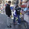 Holly Holland, right, hugs her daughter Katie, center, as her husband Kevin Holland, left, all of St. Louis, looks while visiting a makeshift memorial in Boston, Monday, April 22, 2013. The memorial sits on Boylston St., not far from where two bombs exploded near the finish line of the Boston Marathon, Monday, April 15, 2013. (AP Photo/Steven Senne)