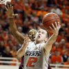 OSU\'s Keiton Page (12) takes a shot in front of Texas A&M\'s Keith Davis (4) in the first half of a men\'s college basketball game between the Oklahoma State University Cowboys and Texas A&M University Aggies at Gallagher-Iba Arena in Stillwater, Okla., Saturday, Feb. 25, 2012. OSU won, 60-42. Photo by Nate Billings, The Oklahoman