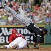 Photo - Los Angeles Angels' Mike Trout slides safely under Chicago White Sox's Micah Johnson as he steals second during the second inning of an exhibition spring training baseball game Thursday, March 13, 2014, in Tempe, Ariz. (AP Photo/Morry Gash)