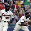 Photo - Atlanta Braves' Jason Heyward, left, celebrates along with teammate Justin Upton, right, after Heyward scored the game winning run off a single by Freddie Freeman in the tenth inning of a baseball game against the Cincinnati Reds, Sunday, April 27, 2014, in Atlanta. The Braves won 1-0. (AP Photo/David Goldman)
