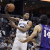 Photo - Memphis Grizzlies' Rudy Gay, left, passes the ball as he is pressured by Phoenix Suns' Luis Scola (14), of Argentina, during the second half of an NBA basketball game in Memphis, Tenn., Tuesday, Dec. 4, 2012. The Grizzlies defeated the Suns 108-98 in overtime. (AP Photo/Danny Johnston)
