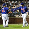 Photo - New York Mets starting pitcher Bartolo Colon (40) greets Lucas Duda (21) at home plate after Duda scored on a ground rule double by Matt den Dekker off of San Diego Padres starting pitcher Andrew Cashner in the fourth inning of a baseball game at Citi Field on Friday, June 13, 2014, in New York. (AP Photo/Kathy Kmonicek)