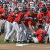 Photo - Mississippi players celebrate their 2-1 win over Texas Tech with teammate John Gatlin (36), who hit the single that scored Aaron Greenwood in the ninth inning, in an NCAA baseball College World Series elimination game in Omaha, Neb., Tuesday, June 17, 2014.  (AP Photo/Ted Kirk)