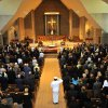 Guests stand at attention as U.S. Naval officers drape Elmore Leonard\'s casket with an American flag during the military honors portion of his funeral mass inside Holy Name Church in Birmingham, Mich., Saturday Aug. 24, 2013. Leonard served in the Navy during World War II. The beloved Metro-Detroit crime novelist died Tuesday at his home in Bloomfield Village at age 87. (AP Photo/The Detroit News, John T. Greilick)