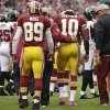 Photo -   Washington Redskins quarterback Robert Griffin III walks off the field after being hit by Atlanta Falcons defensive end Jonathan Massaquoi during the second half of an NFL football game in Landover, Md., Sunday, Oct. 7, 2012. (AP Photo/Evan Vucci)