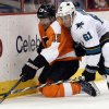Photo - Philadelphia Flyers' Scott Hartrnell, left, and San Jose Sharks' Justin Braun, right, dig for the puck along the boards during the second period of an NHL hockey game on Thursday, Feb. 27, 2014, in Philadelphia. (AP Photo/Tom Mihalek)