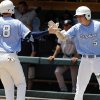 North Carolina\'s Colin Moran (18) is congratulated by Michael Russell (5) after scoring in the sixth inning of an NCAA college baseball tournament super regional game against South Carolina in Chapel Hill, N.C., Tuesday, June 11, 2013. North Carolina won 5-4 to advance to the College World Series. (AP Photo/Gerry Broome)