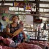 In this April 4, 2013 photo, Aye Aye Khine, right, sits beneath two 969 logos she hangs above her meat shop at the Kyimyindaing market in Yangon, Myanmar. She made the signs herself, copying them from the cover of a 969 DVD a friend gave her.