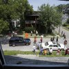 East Cleveland residents gather outside abandoned house to help search for more bodies Sunday, July 21, 2013, in East Cleveland, Ohio. Police Chief Ralph Spotts told volunteers checking vacant houses in a neighborhood where three bodies were found wrapped in plastic bags that he believes there could be one or two more victims. (AP Photo/Tony Dejak)