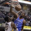 Oklahoma City Thunder forward Kevin Durant, right, dunks over Indiana Pacers center Roy Hibbert in the first half of an NBA basketball game in Indianapolis, Friday, April 6, 2012. (AP Photo/Michael Conroy) ORG XMIT: NAF101