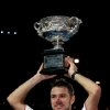Photo - Stanislas Wawrinka of Switzerland holds up  the trophy after defeating Rafael Nadal of Spain in the men's singles final at the Australian Open tennis championship in Melbourne, Australia, Sunday, Jan. 26, 2014. (AP Photo/Aaron Favila)