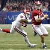Alabama\'s AJ McCarron (10) runs past Oklahoma\'s Charles Tapper (91) during the NCAA football BCS Sugar Bowl game between the University of Oklahoma Sooners (OU) and the University of Alabama Crimson Tide (UA) at the Superdome in New Orleans, La., Thursday, Jan. 2, 2014. .Photo by Chris Landsberger, The Oklahoman
