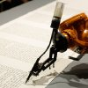 Photo - A robot writes a Torah at an installation in the Jewish Museum in Berlin, Germany, Thursday, July 10, 2014. It is an installation by the artist group robotolab. The robot is equipped with a pen nib and ink and will write the Torah in human speed. (AP Photo/Markus Schreiber)