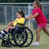 AshLynne Prigmore, age 10, of Yukon, pushes her sister MaKenna Prigmore, age 8, from second base to third base during the first Spirit League Game at the Yukon Commnunity Center in Yukon, Okla., on Tuesday July 8, 2008. By John Clanton, The Oklahoman