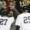 New York Yankees Alex Rodriguez, middle, welcomes teammates Raul Ibanez, left, and Mark Teixeira after Ibanez hit a two-run home run in the month inning of Game 1 of the American League championship series Saturday, Oct. 13, 2012, in New York. (AP Photo/Matt Slocum)