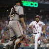 Photo - San Francisco Giants catcher Buster Posey, left, stands at home plate as Washington Nationals' Anthony Rendon scores on an error by second baseman Joe Panik during the first inning of a baseball game on Friday, Aug. 22, 2014, in Washington. (AP Photo/Evan Vucci)