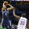 Photo - Memphis Grizzlies forward Tayshaun Prince (21) shoots over Oklahoma City Thunder forward Kevin Durant (35) during the first quarter of an NBA basketball game in Oklahoma City, Friday, Feb. 28, 2014. (AP Photo/Sue Ogrocki)