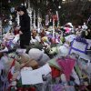 Jeanne Walker of Newtown walks through an overflowing memorial to the shooting victims in the Sandy Hook village of Newtown, Conn., Thursday, Dec. 20, 2012. Adam Lanza walked into Sandy Hook Elementary School in Newtown, Dec. 14, and opened fire, killing 26 people, including 20 children, before killing himself. (AP Photo/Seth Wenig)