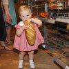 """Photo -  Hattie McWhorter, 1, helps herself to a loaf of bread in the grocery store section of the """"Hungry Planet: What the World Eats"""" exhibition at the Sam Noble Oklahoma Museum of Natural History. PHOTO BY LYNETTE LOBBAN, FOR THE OKLAHOMAN"""