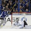 Photo - Tampa Bay Lightning right wing Martin St. Louis (26) scores past San Jose Sharks goaltender Antti Niemi (31), of Finland, during the first period of an NHL hockey game Saturday, Jan. 18, 2014, in Tampa, Fla. (AP Photo/Chris O'Meara)