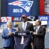 Photo - New England Patriots owner Robert Kraft, left, and team president Jonathan Kraft, right, present Jamie Collins, center, with a jersey representing the team's first NFL football draft pick at Gillette Stadium in Foxborough, Mass., Thursday, May 2, 2013. The Patriots took Collins with the 52nd overall pick, after Belichick privately worked with him. (AP Photo/Steven Senne)