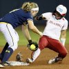 OU\'s Destinee Martinez (00) makes it safely to second base as Michigan\'s Ashley Lane (8) loses her shoe in the second inning during an NCAA softball game in the Women\'s College World Series between Oklahoma and Michigan at ASA Hall of Fame Stadium, Thursday, May 30, 2013. Photo by Nate Billings, The Oklahoman